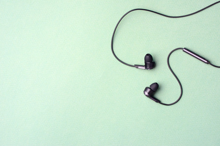 Headphones with wires and a control panel lie on a mint-green background.
