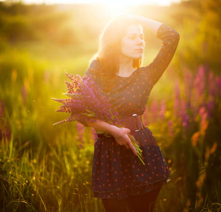 Young adult woman in green dress with bouquet of lupines in hands against a background of flowering meadow. Sunlight on the face. Spring, Summer. Beautiful morning, evening lighting. Square 1:1 shot Stock Photo