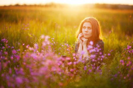 A young adult European girl with long fair-haired hair sits on a flowering meadow, holding her hands in front of her face. Pink flowers in the foreground. Beautiful morning light. Stock Photo