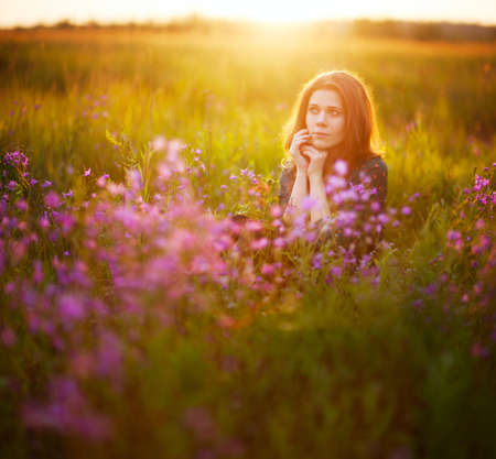 A young adult European girl with long fair-haired hair sits on a flowering meadow, holding her hands in front of her face. Pink flowers in the foreground. Beautiful morning light. Square 1:1 shot Stock Photo