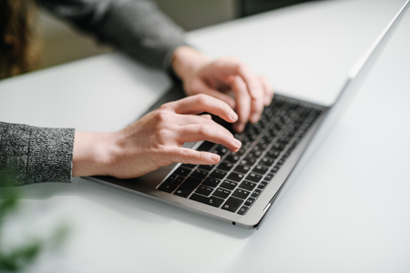 Hands of a young woman typing text on the laptop keyboard. Gray clothes. Woman working at home office hand on keyboard close up. White table, shallow depth of field.