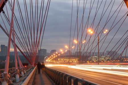 Zhivopisny Bridge at night, in the evening. City lights. Night city. Light traces. Silhouettes of people walking. Moscow, Russia