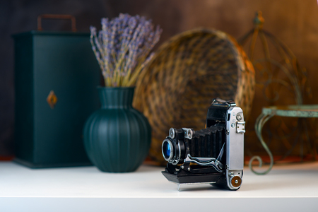 Vintage camera with bellows, accordion on a white table. Old things, a bouquet of lavender in a vase blurred background.