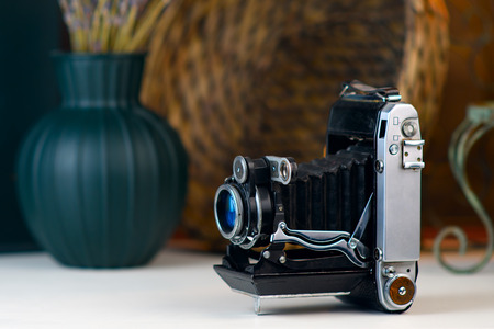 Vintage camera with bellows, accordion on a white table. Old stuff on blurred background.  Stock Photo