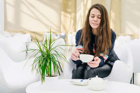 Young attractive woman with a cup of tea in a cafe. A kettle and a saucer on the table. Smiling, looking down. Bright modern interior. A potted plant in a pot on the table. Natural unconventional beauty. Stock Photo