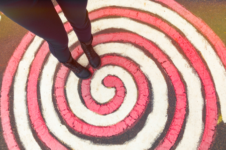 Fun, amusement, joking, crazy mood concept. Female feet in boots stand on a painted red and white spiral on the floor.