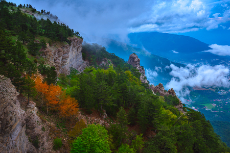 Mountains covered with forest in the clouds, quaint rocks. Settlements at the foot of the mountains. Taraktash Gorge, the Republic of Crimea