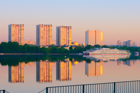 A view of the citys high-rise buildings, the river. City outskirts. Embankment. Summer, good weather. Ships on the river. Morning, evening lighting. Moscow, Northern River Port.