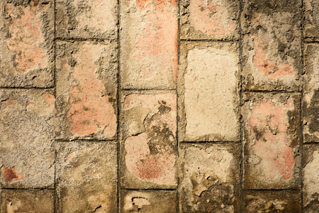 Texture of an old brown brick wall. Peeling paint. Bricks stand vertically