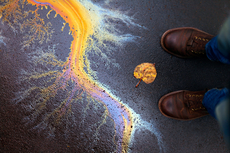 Ecological problems. Careless attitude to nature. Environment protection concept. Colorful rainbow oil stain on the floor asphalt, yellow dead autumn leaf, mans shoes.