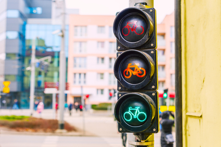 A traffic light for a bicycle. At the traffic light for a bicyclist, a green light is on. Cyclists in traffic. Rules of the road for a bicycle.