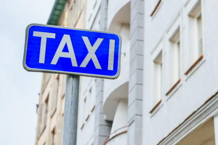 Road sign taxi on a background of a light building. A word of a taxi on a blue road sign sign. Stock Photo