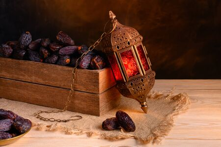 Ramadan concept. Dates close-up in the foreground. Box with dates and ramadan lantern on a wooden table. Dark textured wall background. Stock Photo