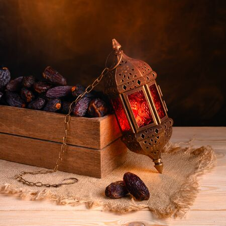 Ramadan concept. Dates close-up in the foreground. Box with dates and ramadan lantern on a wooden table. Dark textured wall background. Square 1:1 frame.