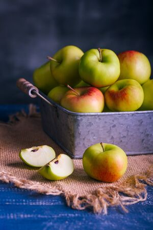 Delicious green apples. In a metal pot. Canvas. Blue textural table, dark background. Healthy natural lifestyle