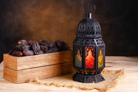 Ramadan concept. Box with dates and ramadan lantern on a wooden table. Dark textured wall background.