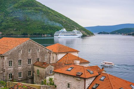 Travel, vacation concept. The cruise ship leaves the bay. In the foreground there are red tiled roofs of the old Adriatic, Mediterranean town. Фото со стока