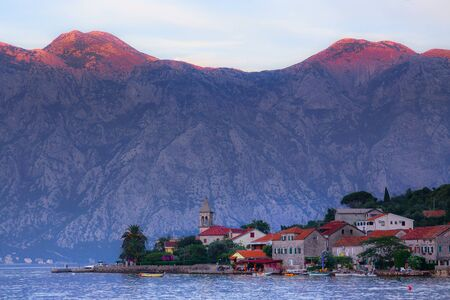 Adriatic, Mediterranean blooming picturesque old town in the background of mountains. Evening sunset lighting. Vacation, vacation, trip to the south. Perast, Kotor Bay, Montenegro.