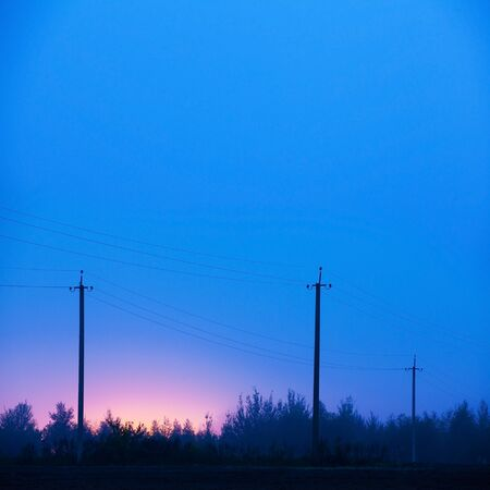 Old power line supports in rural areas. Night, fog. Electric poles in the mist, Russian countryside. Stock Photo
