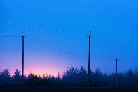 Old power line supports in rural areas. Night, fog. Electric poles in the mist, Russian countryside. Imagens