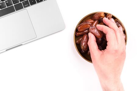 Modern muslim lifestyle. Holy month of Ramadan. A man's hand reaches out to a plate with dates near the laptop. Traditions and modernity concept.