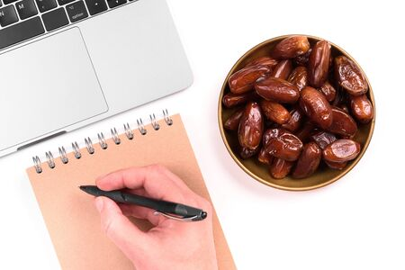 Modern muslim lifestyle. Holy month of Ramadan concept. A man's hand makes notes in a notebook. Nearby is a plate with dates and a laptop.Traditions and modernity. Stock Photo