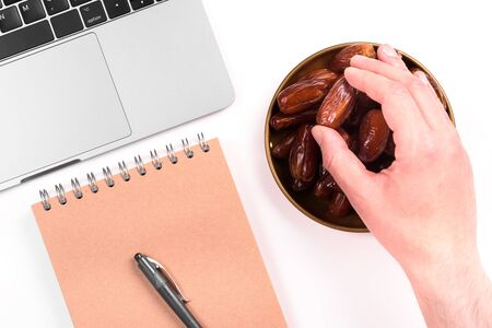 Modern muslim lifestyle. Holy month of Ramadan. A man's hand reaches out to a plate with dates. Laptop and notebook and pen. Traditions and modernity.