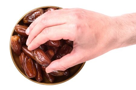 A man's hand reaches out to a plate with dates. Isolated on white background. Holy month of Ramadan. Righteous Muslim Lifestyle