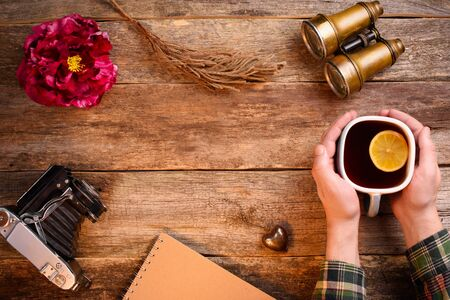 Old wooden surface, empty space in the center for text. Copy space. Hands holding a cup of tea with a lemon. Binoculars, old camera, notebook, red peony flower. Mockup. Stock Photo