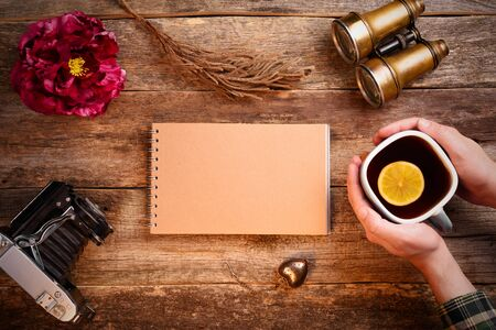 Notepad with blank page of kraft paper in the center of the frame. Old wooden table. Hands holding a cup of tea with a lemon. Binoculars, old camera, notebook, red peony flower. Mockup. Stock Photo