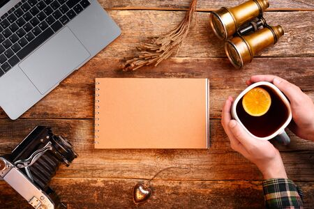 Notepad with blank page of kraft paper in the center of the frame. Old wooden table. Hands holding a cup of tea with a lemon. Binoculars, old camera, notebook, laptop. Mockup.