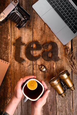 The word tea spelled using brown letters on the wooden table. Hands with a cup of tea with a lemon. Binoculars, old camera, tea sieve, notebook laptop. Comfort, healthy lifestyle, travel concept. Stock Photo