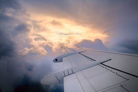 Traveling by plane concept. View from the porthole. Beautiful cloudscape sunset outside the window. Airplane wing in flight. Stock Photo