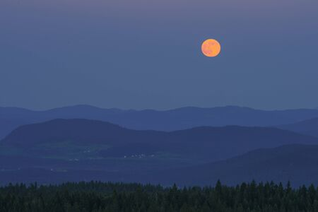 Orange full moon over the forest and hills, twilight
