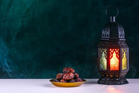 Holy month of Ramadan concept. Burming, lighting, glowing Ramadan Lantern, dates on white table on the background of a dark green textured wall. Greetings card. Place for text on the left.