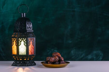Holy month of Ramadan concept. Burming, lighting, glowing Ramadan Lantern, dates on white table on the background of a dark green textured wall. Greetings card. Place for text on the right