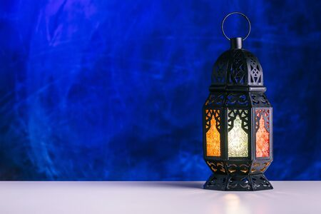 Holy month of Ramadan concept. Burming, lighting, glowing Ramadan Lantern on white table on the background of a dark blue textured wall. Greetings card. Place for text on the left.
