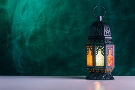 Holy month of Ramadan concept. Burming, lighting, glowing Ramadan Lantern on white table on the background of a dark green textured wall. Place for text on the left.