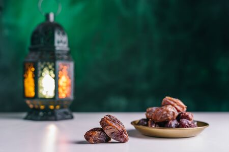 Holy Ramadan concept. Dates close-up in the foreground. On the distant plan a slightly blurry Burning, lighting, glowing Ramadan Lantern on a white table, textured dark green wall background. Place for text on the right