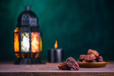 Ramadan concept. Dates in the foreground. On the distant plan a blurry Burning, glowing Ramadan Lantern and candle on a wooden table. Green textured wall background.  Place for text on the right