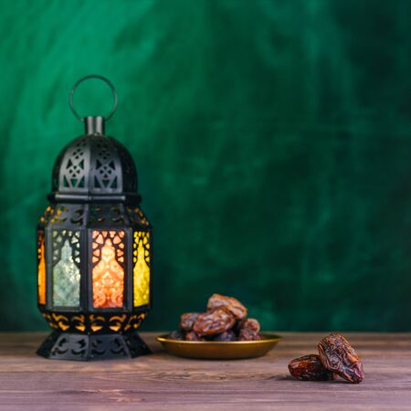 Ramadan concept. Dates close-up in the foreground. On the distant plan a blurry Ramadan Lantern on a wooden table. Textured green wall background. Space for text on the right. Square 1:1 frame. Stock Photo