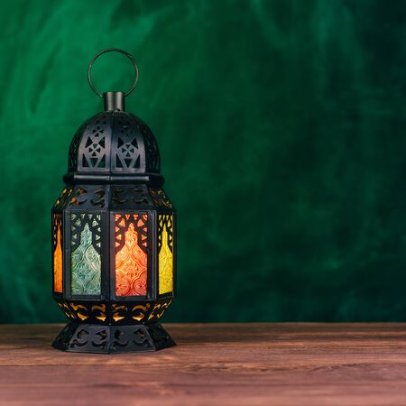 Holy month of Ramadan concept. Burning, lighting, glowing Ramadan Lantern on a wooden table on the background of a textured wall of green color. Greeting card. Place for text on the right. Square 1: 1 frame