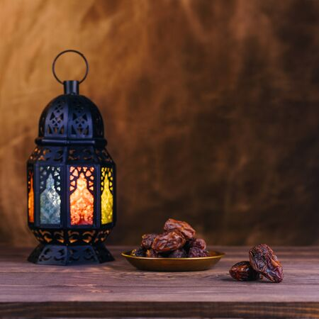 Ramadan concept. Dates close-up in the foreground. On the distant plan a blurry Ramadan Lantern on a wooden table. Textured yellow wall background. Space for text on the right. Square 1:1 frame. Stock Photo