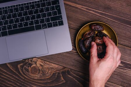 Holy Ramadan concept. Copper plate with dates near the laptop. The hand reaches for the dates. Traditions and modernity. Muslims at the computer, on the Internet. Righteous Islam lifestyle