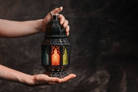 Burning, glowing, lighting Ramadan lantern in hands at the background of a dark black textured wall. Horizontal shot. Empty space on the right. Stock Photo