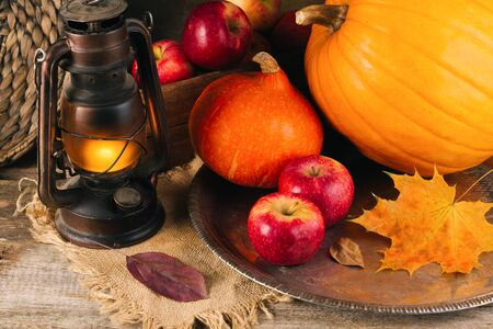 Autumn mood concept. Harvest stillife pimpkin, apples, gas lantern, yellow maple leaf. Old wooden table