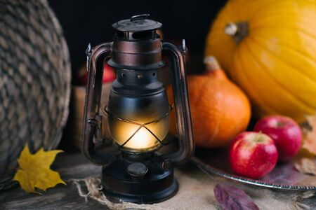 Autumn mood concept. Selective focus on the gas lamp. Harvest stillife pimpkin, apples, lantern, yellow maple leaf. Old wooden table.