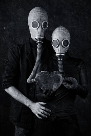 We breathe through love concept. A pair of gas masks connected to a metal heart. Gothic, metal music style. Vertical black and white shot.