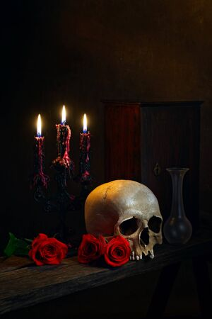 A human skull, red roses, burning candles on the old wooden table. Dark atmosphere. Gothic concept. Vanitas, death