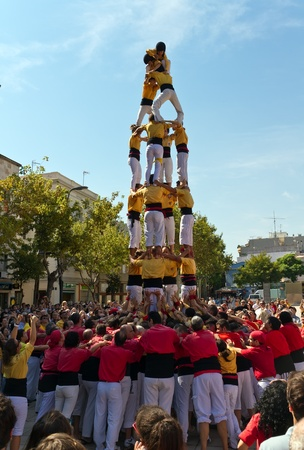 BARCELONA - SEPTEMBER 11: Some unidentified people called Castellers do a Castell or Human Tower, typical tradition in Catalonia, on September 11, 2011 in Badalona, Spain.